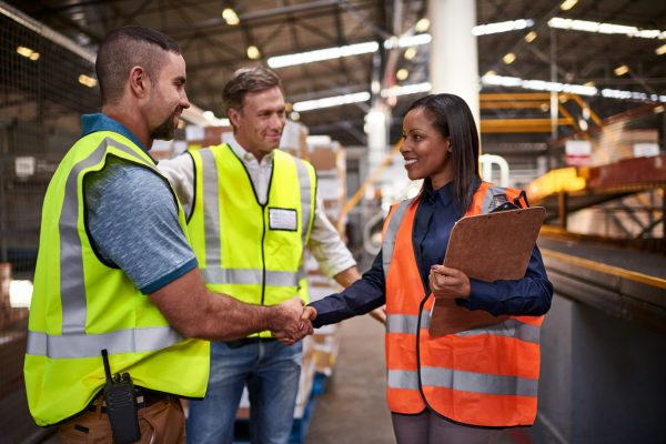 Shot of two workers shaking hands together while standing in a large warehouse