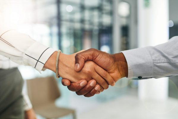 Closeup shot of two businesspeople shaking hands in an office