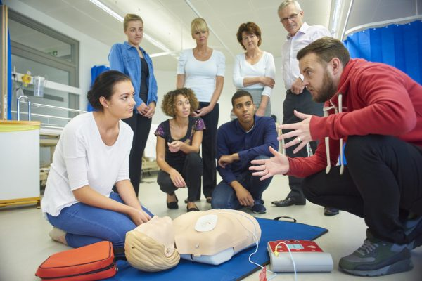 a mixed age group listen to their tutor as he shows the procedure involved to resuscitate using a defibrillator .