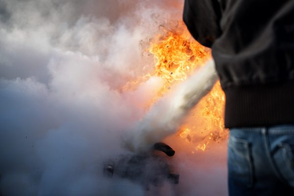 man from behind is fighting a fire with foam from a fire extinguisher, copy space in the smoke