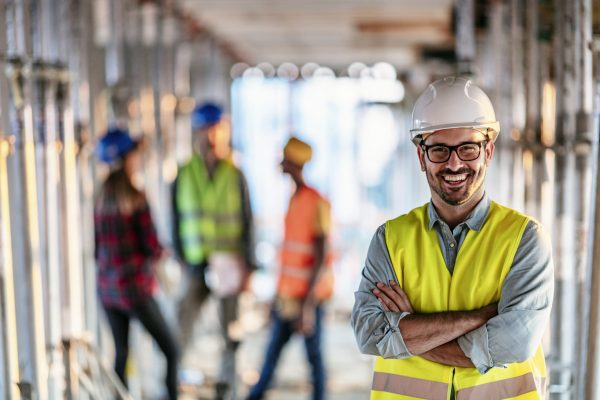 Photo of business people group on meeting and presentation in bright modern office with construction engineer architect and worker looking building model. Front view of smiling architect in helmet against his three colleagues.